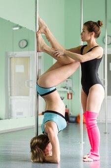 Schöne mädchen mit einem pylon, weibliche stangentänzer, die auf einer stange tanzen.