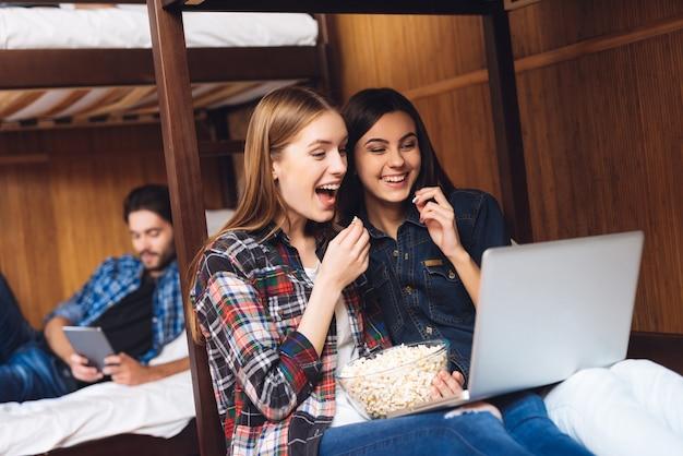 Schöne mädchen sitzen auf dem bett und schauen sich gemeinsam einen film an.