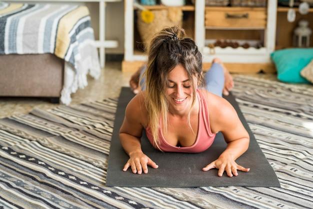 Schöne mädchen sport zu hause fitness-übung abs intelligentes training übung zu hause trainieren push-up ausgeglichene position für gesunde lebensstil menschen konzept und indoor-sport routine freizeitaktivität
