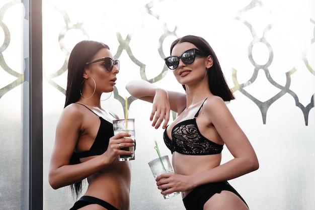 Schöne mädchen trinken cocktails am strand