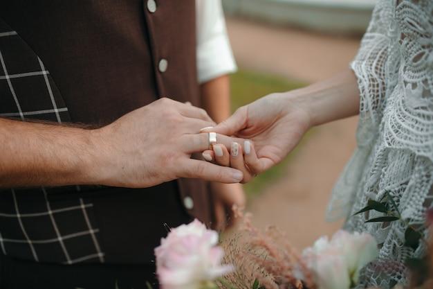 Schöne mädchenbraut im weißen hochzeitskleid legt auf den finger des bräutigams den eheringgoldring
