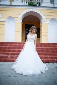 Schöne mädchenbraut in einem weißen kleid mit einem zug, der an ihrem hochzeitstag auf dem hintergrund eines großen hauses mit säulen geht