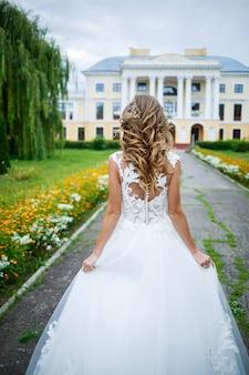Schöne mädchenbraut in einem weißen kleid mit einem zug und einem spaziergang vor dem hintergrund eines großen hauses mit säulen an ihrem hochzeitstag house