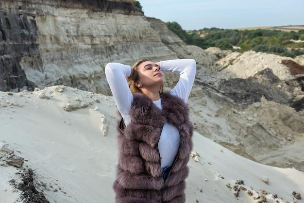 Schöne mädchenbrünette in t-shirt und shorts ocer pelzmantel, der an leeren sandfelsen aufwirft