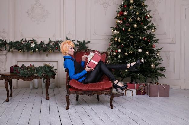 Schöne mädchenfrau nahe dem weihnachtsbaum, der im verzierten haus, guten rutsch ins neue jahr sitzt