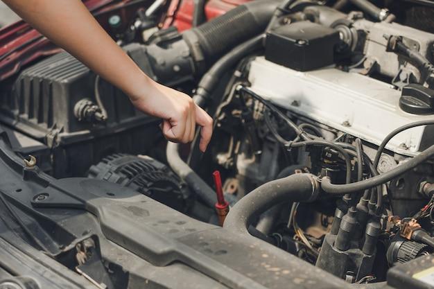Schöne mädchenhände öffnen den autorock, um den ölstand des autos zu überprüfen