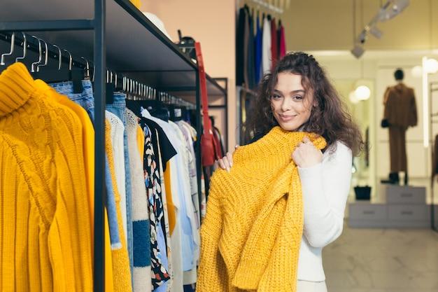 Schöne mädchenkäuferin, die schöne stilvolle kleidung in einer boutique anprobiert und kauft