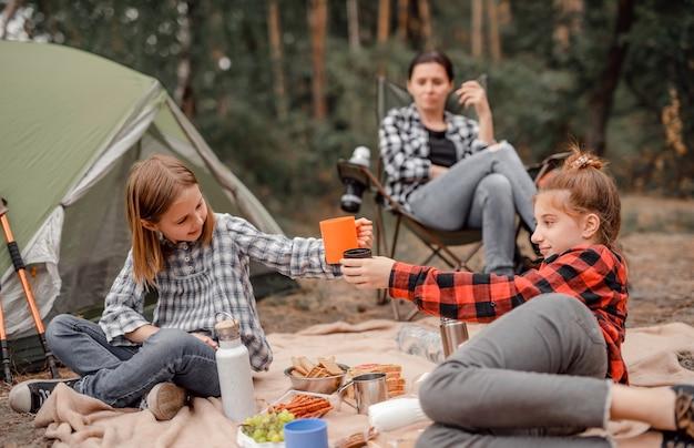 Schöne mädchenschwestern trinken tee beim camping im wald mit zelt und lächeln, während ihre mutter s...