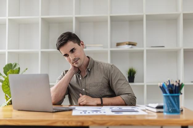 Schöne männer sind müde vom langen sitzen vor dem computer. geschäftsleute leiden oft unter muskel- und augenbelastungen durch lange arbeitszeiten vor einem computerbildschirm.