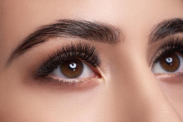 Schöne makrofotografie eines frauenauges mit extremem make-up der langen wimpern.