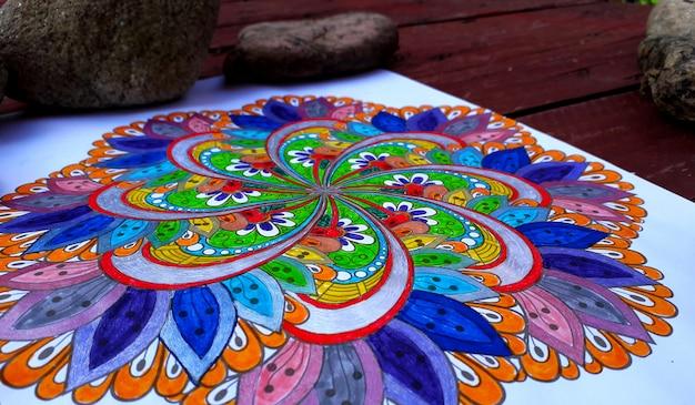 Schöne mandala hand bemalt mit vielen farben und mit einigen steinen im hintergrund