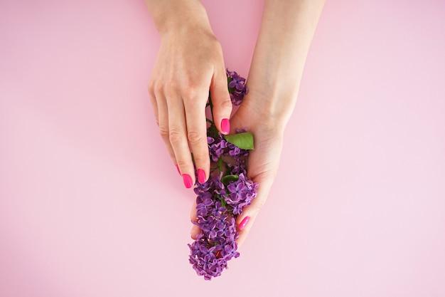 Schöne maniküre, flach gelegen. schönheits- und hautpflegekonzept. schöne weibliche hände und ein zweig flieder auf einem rosa hintergrund.