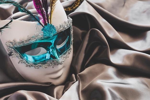 Schöne maske mit federn auf seide