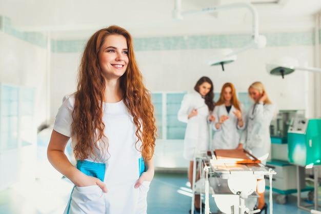 Schöne medizinstudentin auf dem hintergrund der gruppe im operationssaal