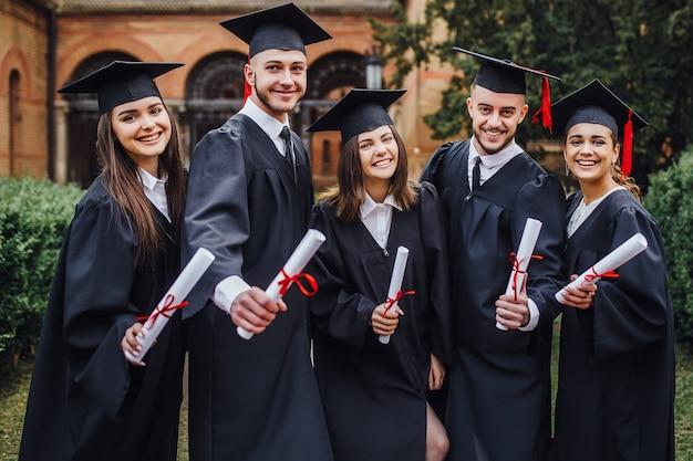 Schöne meister mit diplom auf händen, die außerhalb des glücklichen endes der universität bleiben