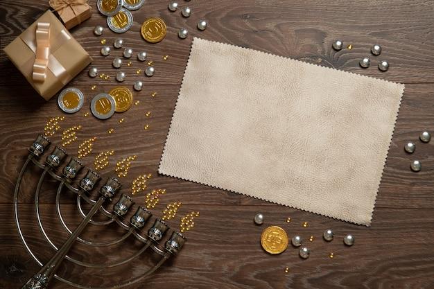 Schöne menora, chanukka-geschenke und ein blatt papier, feiertagsgrüße. draufsicht