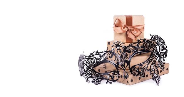 Schöne metallkarnevalsmaske und stapel von geschenkboxen