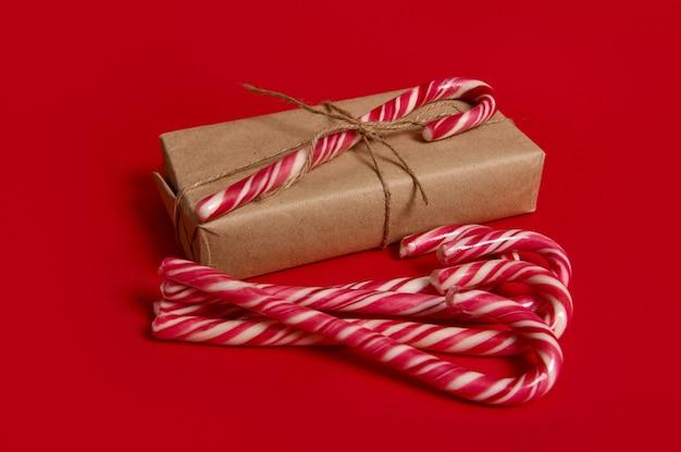 Schöne minimalistische komposition von weihnachtsartikeln, geschenkbox in kraftpapier verpackt mit gebundener schleife und süßen zuckerstangen einzeln auf rotem hintergrund mit kopienraum für werbung