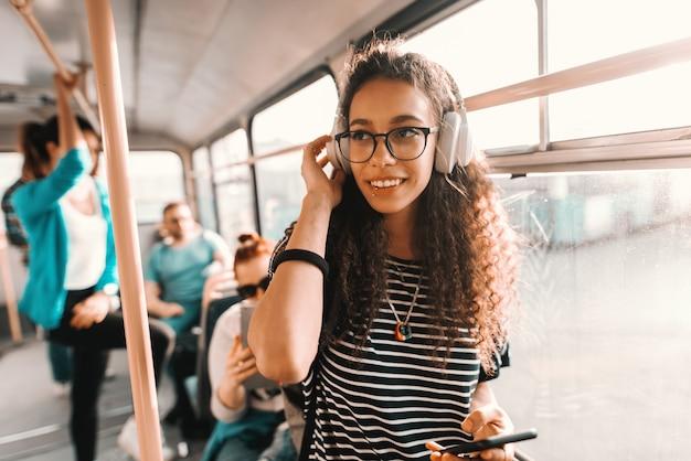 Schöne mischlingsfrau, die musik hört, mit smartphone und im öffentlichen verkehr stehend.
