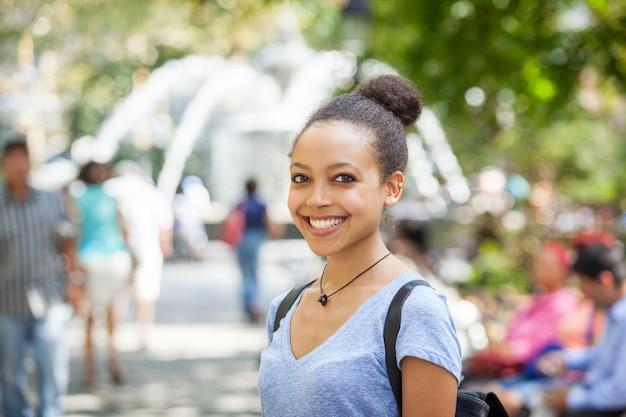 Schöne mischrasse-junge frau am park, lächelndes porträt