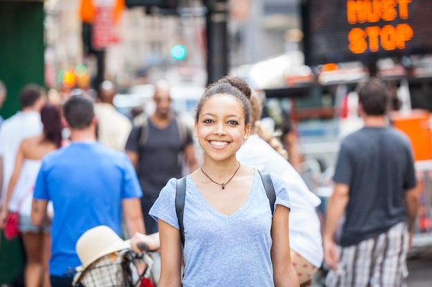 Schöne mischrasse-junge frau in der stadt, lächelndes porträt