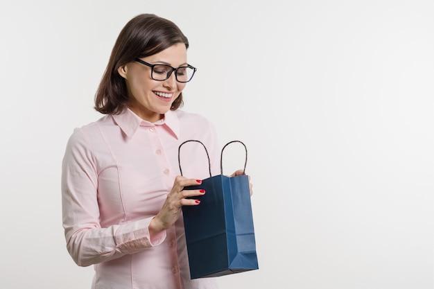Schöne mittlere gealterte frau, die eine einkaufstasche öffnet
