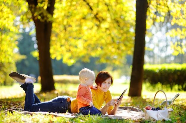 Schöne mittlere greisin und ihr entzückender kleiner enkel, die ein picknick im sonnigen park hat. familie, die zusammen tabletten-pc verwendet