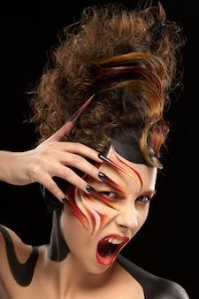 Schöne mode frau farbe gesicht kunst fenix stil und nageldesign. aggressive emotionen.
