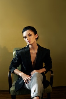 Schöne mode nackte selbstbewusste frau mit schwarzen haaren rauchen einer zigarette sitzt auf einem stuhl in einer schwarzen jacke. perfekter körper, glatte, saubere haut. stilvolles porträt einer frau