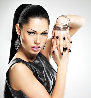 Schöne mode sexy frau mit schwarzen nägeln am hübschen gesicht. hübsches mädchenmodell mit stilvoller bijouterie der silbernen farbe.