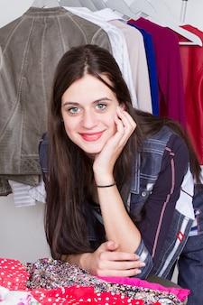 Schöne modedesignerdamenschneiderin, die an ihren designen im stilvollen ausstellungsraum des studios arbeitet