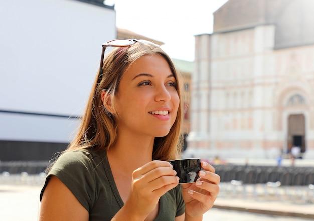 Schöne modefrau, die im freiencafé in italien sitzt, das kaffee trinkt