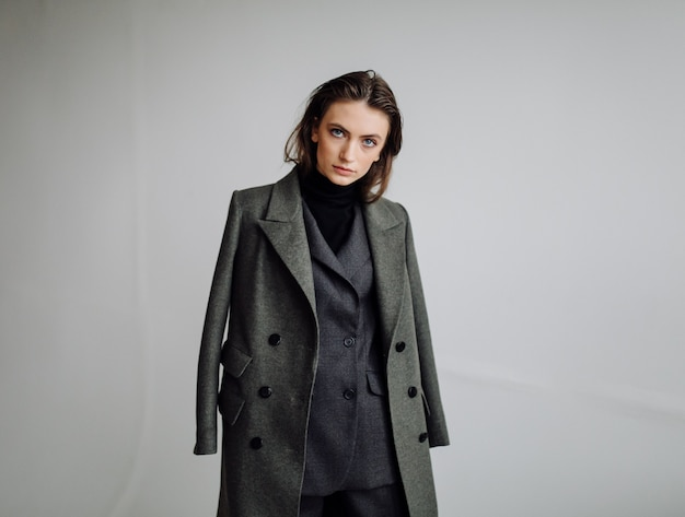 Schöne modefrau, die mit elegantem anzug aufwirft