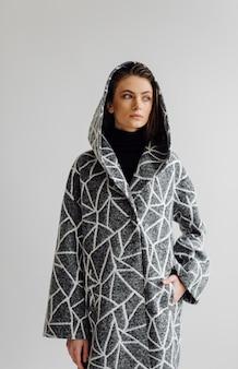 Schöne modefrau, die mit elegantem mantel aufwirft