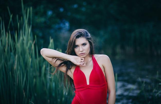 Schöne modefrau im roten bikini, der im sommerstrand aufwirft