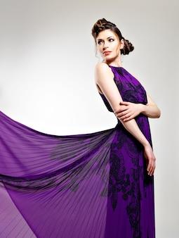 Schöne modefrau in der violetten langen kleidfrisur mit zopfentwurf, wirft im studio auf