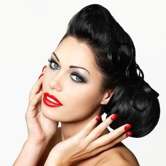 Schöne modefrau mit roten lippen, nägeln und kreativer frisur - lokalisiert auf weißer wand
