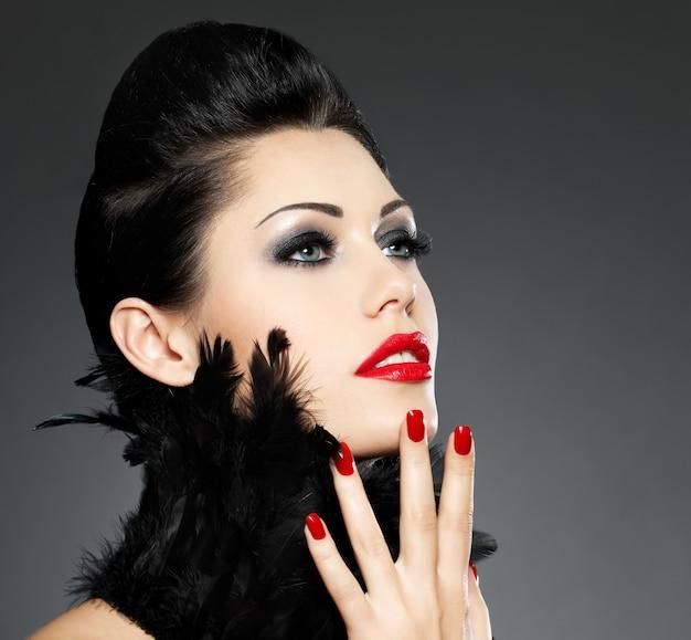 Schöne modefrau mit roten nägeln, kreativer frisur und make-up