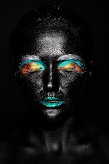 Schöne modellfrau mit kreativem kunststoff ungewöhnliche schwarze maske helles buntes make-up mit schwarzem gesicht