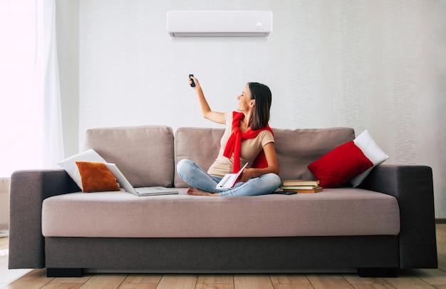 Schöne moderne brünette frau benutzt die klimaanlage, während sie auf der couch sitzt und sich an dem heißen tag ausruht