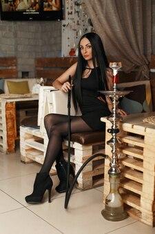 Schöne moderne frau in einem eleganten kleid raucht eine wasserpfeife