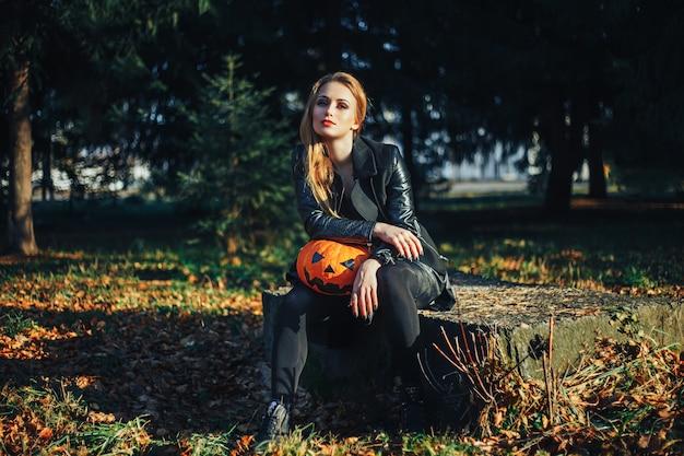 Schöne moderne hexe, die halloween-kürbis im wald hält