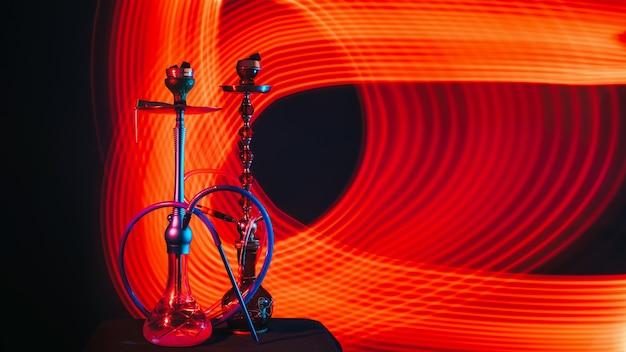 Schöne moderne wasserpfeifen mit heißen shisha-kohlen in schalen auf dem tisch auf einem dunklen hintergrund mit rotem neonlicht