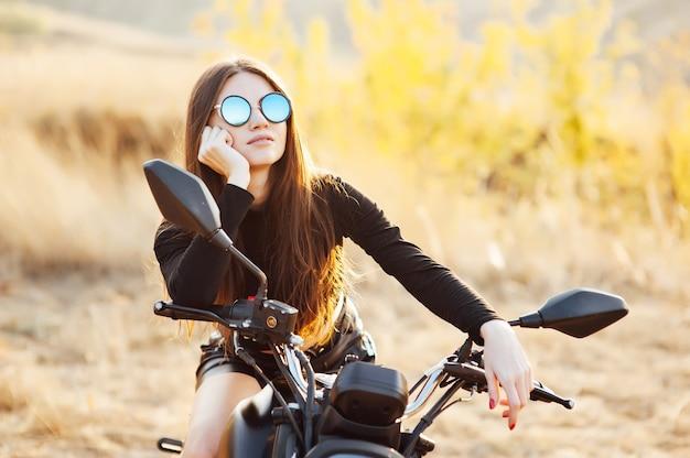 Schöne modische frau auf einem klassischen motorrad, modellauftritt mit sonnenbrille.