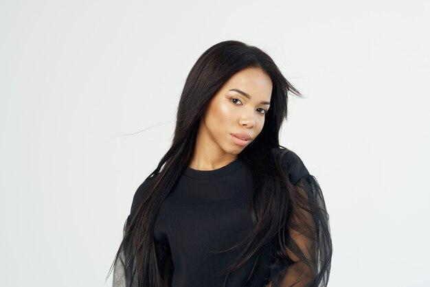 Schöne modische frau des afrikanischen aussehens dunkles hemd langes haar heller hintergrund light