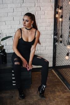 Schöne modische frau im loftstilzimmer mit weißer backsteinmauer und schwarzem eisennetz. attraktives mädchen mit perfekter figur in stilvoller schwarzer kleidung.
