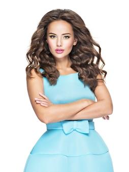 Schöne modische frau mit langen haaren im blauen kleid. attraktives modemodell, das auf weißem hintergrund aufwirft.