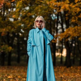 Schöne modische geschäftsfrau mit sonnenbrille im modischen blauen mantel, die in einem herbstpark mit leuchtend buntem herbstlaub telefoniert