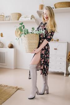 Schöne modische junge frau mit langen blonden lockigen haaren in einem geblümten kleid und stiefeln bleiben in einem gemütlichen innenraum und halten einen weidenkorb mit eukalyptus.
