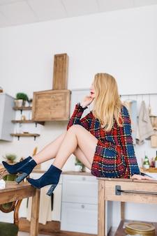 Schöne modische junge frau mit langen blonden lockigen haaren in einem karierten kleid und modischen blauen stiefeletten sitzt auf einem tisch in einem gemütlichen kücheninterieur.